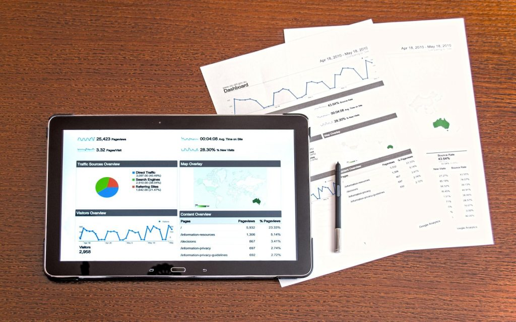 tablet showing a business dashboard and paper reports on a table