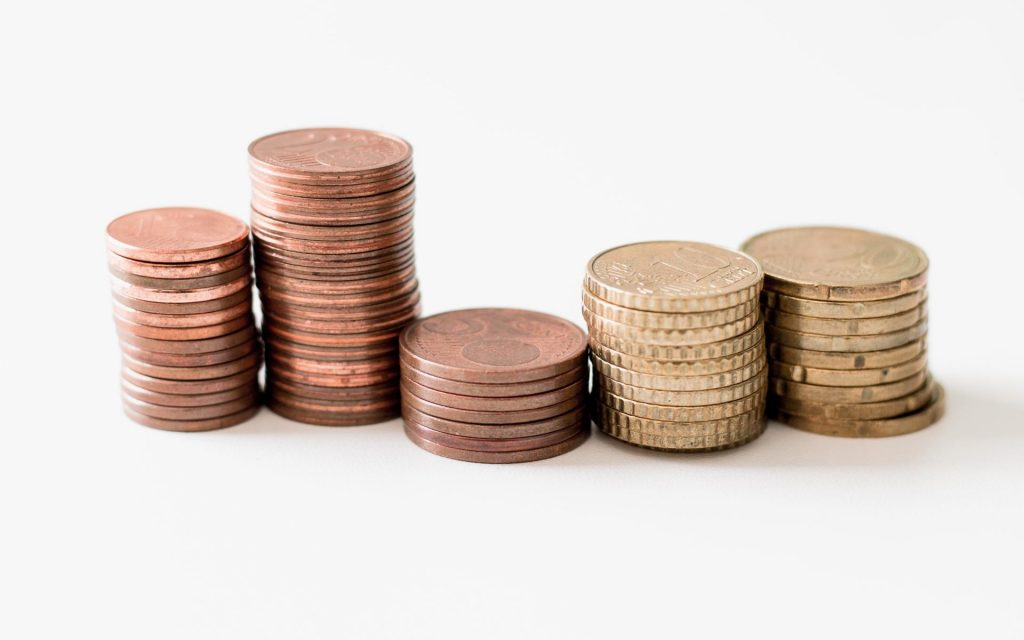 Coins on a surface represent financing for companies based on revenue generated.
